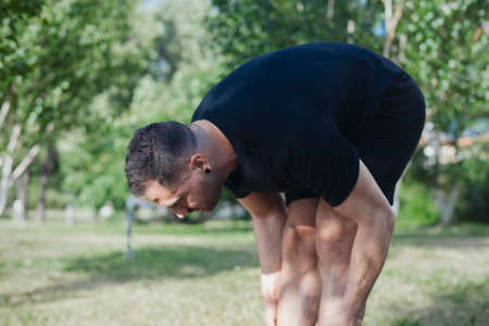 Attractive man doing stretching exercises outdoors in park.