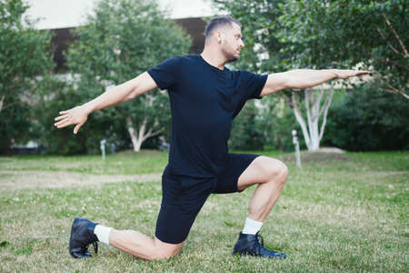 Young attractive man doing lunge outdoor in the park with outstretched hands.