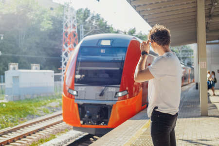 Distant plan of young attractive man waiting train in metro station.