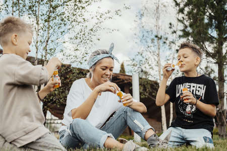 Close up of happy family blowing bubbles outdoors. Young blonde woman and two boys spending weekend in the park and having fun.