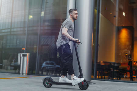 Attractive man riding a kick scooter at cityscape background. Stock Photo