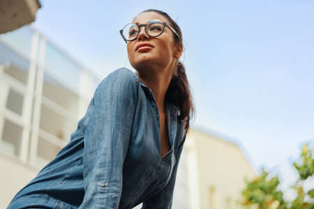 Close up of young attractive bespectacled woman looking aside. Stock Photo