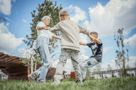 Young blonde mum turning around, whirling with her sons at park. Archivio Fotografico
