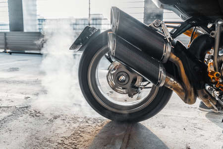 Close up of motorcycle wheel burnout at parking.