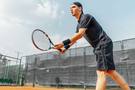 Young man playing tennis at tennis and serving a ball with straighten strike.