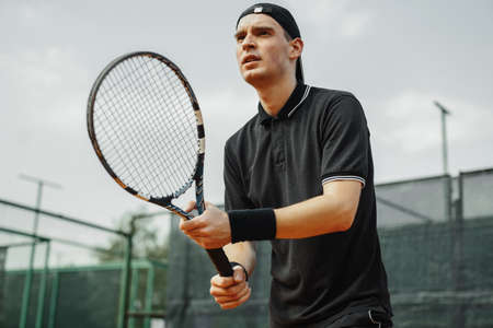 Close up of man holding tennis racket in both hands to straighten strike.