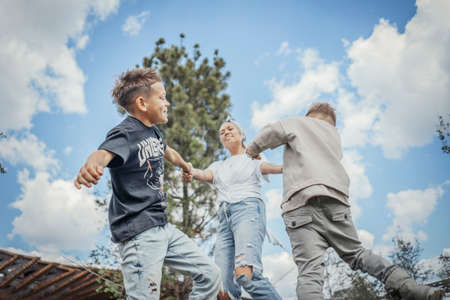 Young blonde mum turning around, whirling with her sons at park. Happy family concept. Family is on foreground and focus, park is blurred.