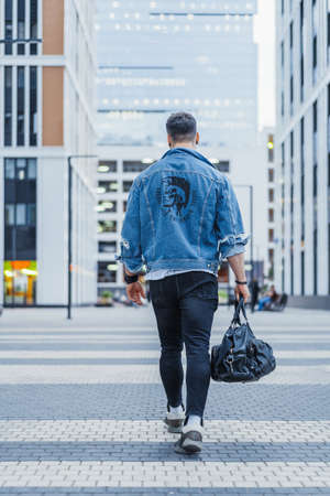 Attractive man passing through modern buildings and holding sports bag. Banque d'images