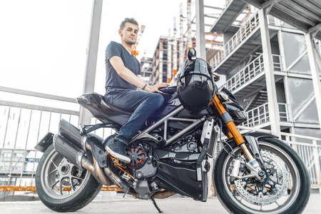 Handsome biker sitting on black motorcycle on urban background at parking.