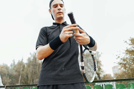 Man putting new grip tape on tennis racket. Wrapping finishing tape on racquet.