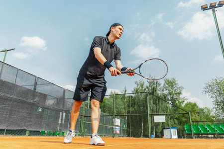 Distant plan of man playing tennis at court and beating the ball with a racket. Stock Photo