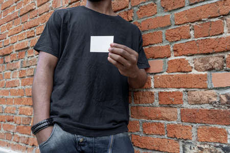 Dark-skinned man in T-shirt showing blank business card on bricked background.