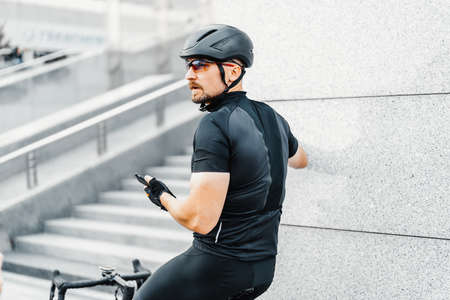 Close up of sportsman relaxing after riding bike next to modern skyscrapers.