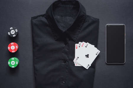 Casino chips, playing cards on formal black shirt and mobile phone on minimalistic black background. Casino game. Online casino. Gambling concept, poker mobile app. Poker game theme. set of four aces Stock Photo