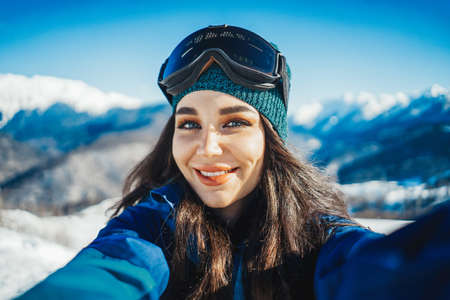 Attractive snowboard girl smiling and making selfie on mountain background.