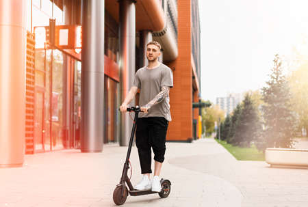 Attractive young man riding contemporary kick scooter at cityscape background.