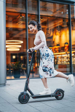 Attractive young woman riding contemporary electric kick scooter at cityscape background.