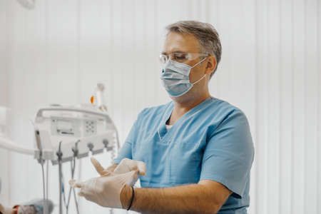 Man dentist sitting next to dental equipment and putting on latex gloves in bright stomatology.