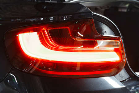 Back headlight car glowing red colour. Luxury modern sport business car.