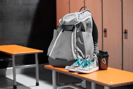 Cerca de calzado deportivo, mochila deportiva y botella de agua deportiva en el vestuario del gimnasio. Concepto de estilo de vida activo, ganando músculos o perdiendo grasa. Equipo de deporte. Foto de archivo