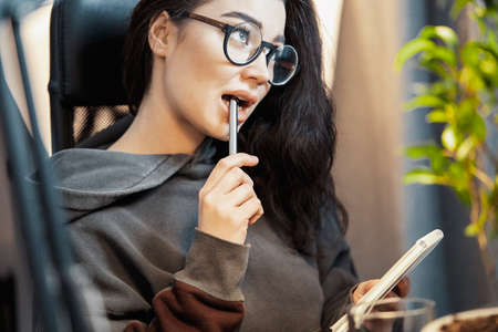 Young attractive woman freelancer writer thinking about text and writing in note pad at home. Concept of freedom and creativity. Home office. Holding pen in mouth and dwelling.