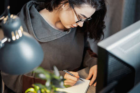 Young attractive woman freelancer writer thinking about text and writing in notepad at home. Concept of freedom and creativity. Home office.