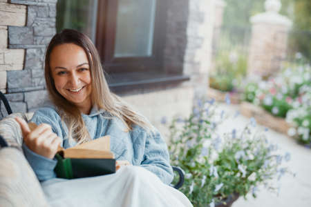 Young woman reading book and smiling next to beautiful big house. Stock Photo