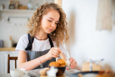 Young cute curly girl preparing breakfast for parents and smiling.