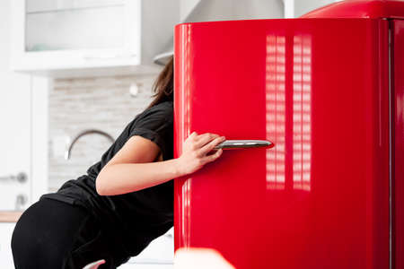 Hungry Woman looking for food in red retro refrigerator in modern bright apartments. Diet keeping concept. Loosing weight or gaining muscles. Evening hunger, Фото со стока - 121510416