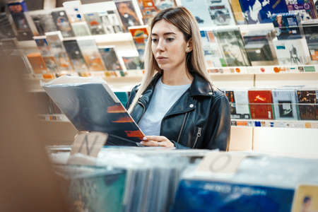 Young attractive woman choosing vinyl record in music record shop. Melomaniac or music addict concept. 免版税图像