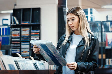 Young attractive woman choosing vinyl record in music record shop. Melomaniac or music addict concept.