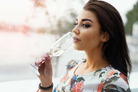 Young beautiful brunette woman in Evening Dress drinking sparkling champagne at the beach in street cafe. Reklamní fotografie