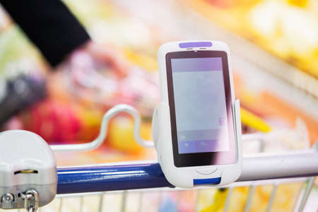 Close up of bar code scanner on shopping cart in store. Man hand with tattoo on background and blurred putting products in cart. Concept of modern gadgets and devices, Consumerism.