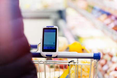 Cerca del escáner de código de barras en el carrito de la compra en la tienda. Concepto de aparatos y dispositivos modernos, consumismo.