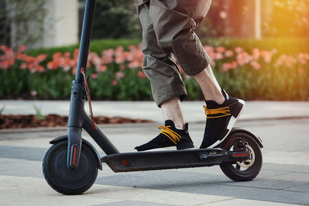 Close up of man riding black electric kick scooter at beautiful park landscape. Man is on foreground, modern building and park is on background.