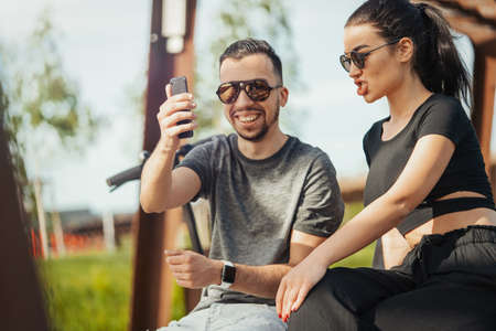 Couple of young man and woman sitting in park and making selfie. Stock Photo