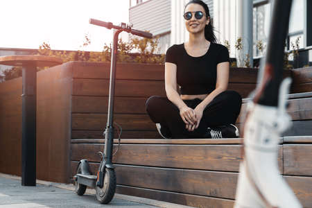 Young attractive woman sitting next to electrick kick scooter at modern park. Stock Photo