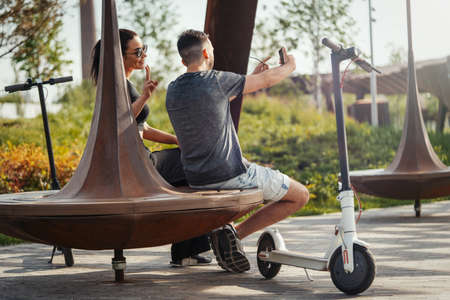 Couple of young man and woman sitting in park and making selfie. Stock Photo - 124901419