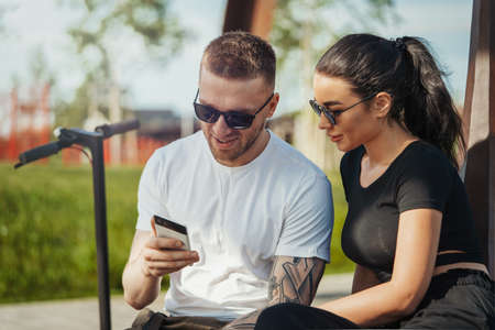 Young man and woman sitting in park and looking at mobile phone screen.
