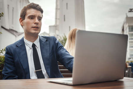 Young attractive businessman sitting at street cafe next to laptop and looking at monitor. Stock Photo