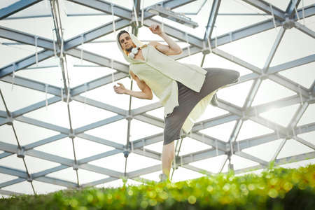 Attractive athletic man practicing yoga and warming up outdoors Stock Photo