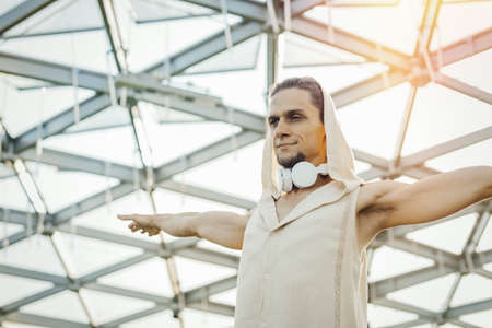 Close up of athletic man practicing yoga in modern park under the glass dome.
