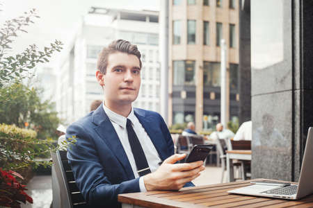 Young businessman sitting next to laptop, holding mobile phone in hand and looking aside. Stock Photo