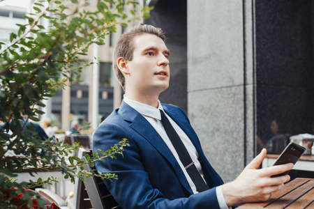 Young businessman holding mobile phone in hand and looking aside. Side view.