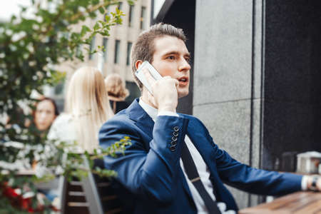 Young pensive attractive businessman talking by mobile phone in street cafe and looking straight.