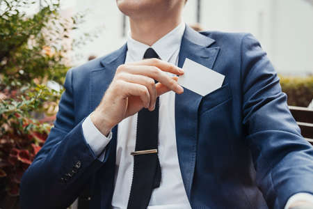 Close up of businessman putting blank business card in his blue jacket pocket. Side view. Stock Photo