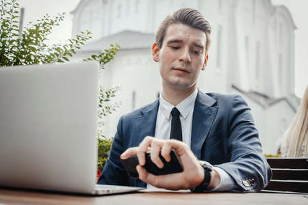 Close up of businessman sitting next to laptop, holding mobile phone in hand and looking at watches. Stock Photo