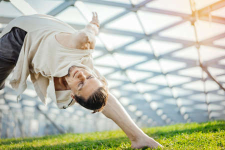 Close up of attractive athletic man practicing yoga and warming up outdoors.