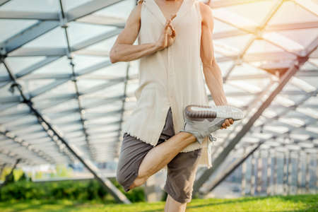 Close up of attractive athletic man practicing yoga and meditating in modern park at green grass outdoors. Фото со стока