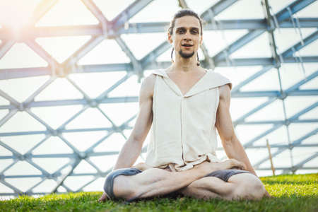 Close up of attractive athletic man practicing yoga and meditating outdoors.
